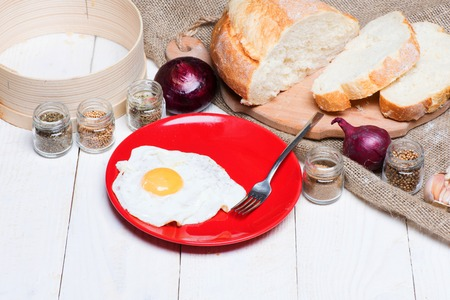 savour: Fried egg on red plate with sliced bread, silver fork, flour sieve, onions and spices for English breakfast near sackcloth on light vintage wooden surface. Homemade concept Stock Photo