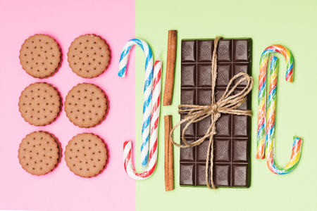 Variety of sweets put geometrically on light green and pink background: chocolate bar, sugar canes, cinnamon sticks and cookies, top view. Happy childhood concept Stock Photo