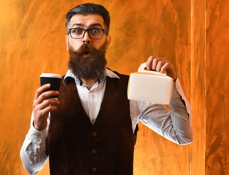 Bearded man, long beard. Brutal caucasian unshaven surprised hipster with glasses and moustache holding black plastic coffee cup or mug and meal box on brown studio background Stock Photo