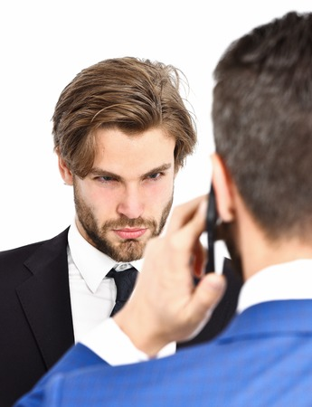 man with angry serious face or businessmen speaking on mobile or cell phone in formal outfit isolated on white