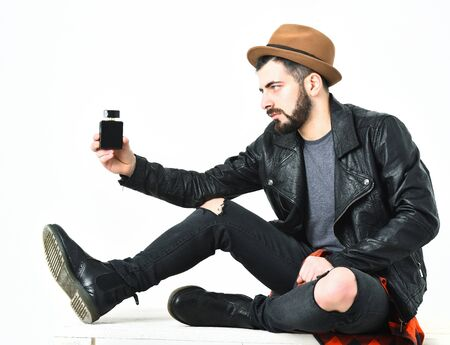 Bearded man, short beard. Caucasian serious hipster with moustache and brown hat holding perfume bottle in black leather jacket, checkered red shirt, ripped jeans isolated on white background Stock Photo
