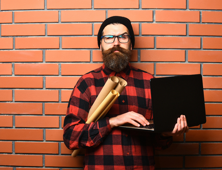 Bearded man, long beard. Brutal caucasian serious unshaven hipster holding laptop and craft paper rolls in red black checkered shirt with hat and glasses on brown brick wall studio background