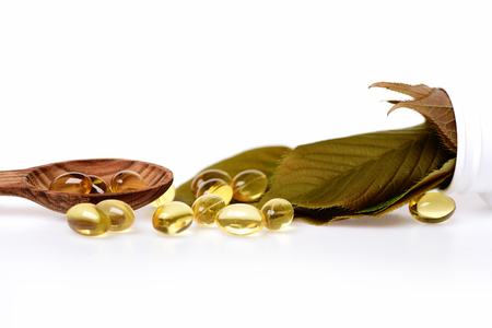 granule: fish oil omega 3 gel capsules isolated on white background in wooden spoon with green leaves, copy space