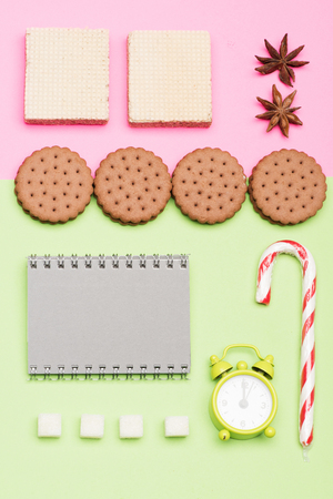 Sweets, alarm clock and copybook put geometrically on light green and pink background