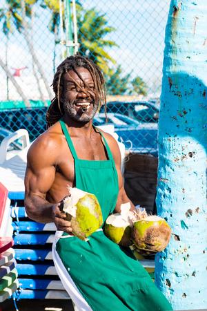 Nassau, Bahamas - January 07, 2016: happy black skinned muscular man with smile break big fresh raw coconut with sharp machete smoking cigar outdoor