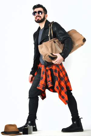 Bearded man, short beard. Caucasian smiling hipster with moustache holding stylish bag, wearing black leather jacket, checkered red shirt and ripped jeans isolated on white background