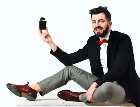 Bearded man, short beard. Caucasian smiling hipster with moustache holding perfume bottle sitting on white wooden bench, wearing black jacket, white shirt and red bow tie isolated on white background Stock Photo