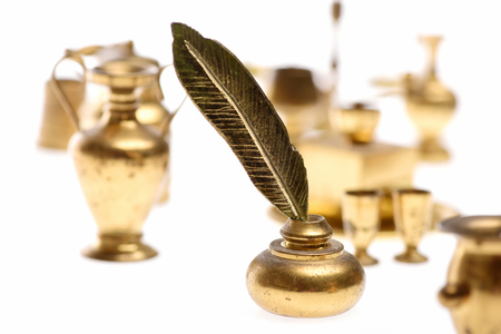 antique vase: Feather pen into inkwell with kitchenware isolated on white background, selective focus