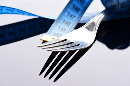 Diet and slim body concept: fork and measuring tape on light grey background with reflection, close up Reklamní fotografie