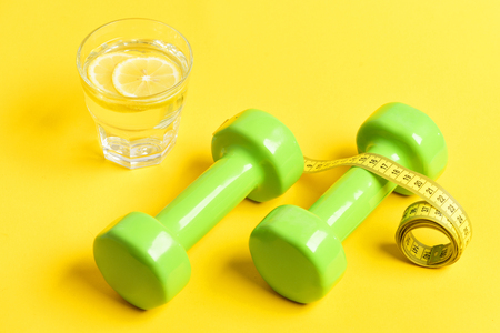 way to lose weight concept. freshly squeezed glass of citrus with dumbbells twined by measuring tape on yellow background