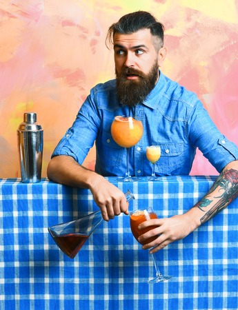Bearded man, long beard. Brutal caucasian surprised hipster with moustache in denim shirt doing cocktails and alcohol shot with bar stuff on blue checkered plaid on colorful texture background