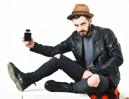 Bearded man, short beard. Caucasian serious hipster with moustache and brown hat holding perfume bottle in black leather jacket, checkered red shirt and ripped jeans isolated on white background