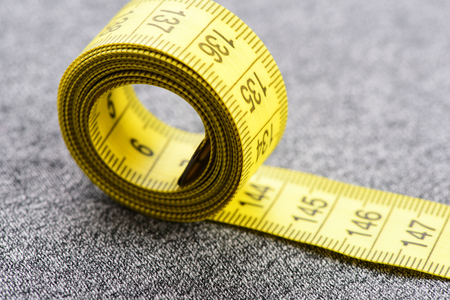 Roll of tape for measuring as symbol of diet in close up. Selective focus Stock Photo