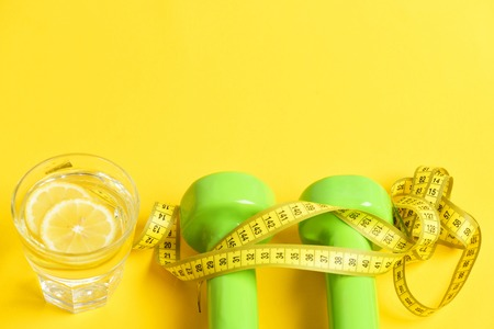 freshly squeezed glass of citrus with dumbbells twined by measuring tape on yellow background, copy space