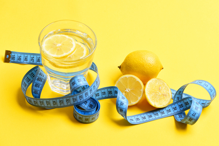 measuring cup: blue centimeter, lemon with freshly squeezed glass of citrus on yellow background. Nutrition and diet concept