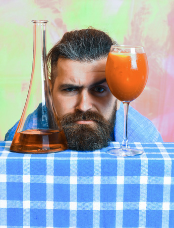 Bearded man, long beard. Brutal caucasian serious hipster with moustache in denim shirt with tropical alcohol fresh cocktail and flask or bottle on blue checkered plaid on colorful texture background