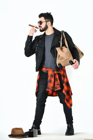 Bearded man, short beard. Caucasian hipster with moustache holding stylish bag and cigar in sunglasses, black leather jacket, checkered red shirt and jeans isolated on white, lookbook concept Stock Photo