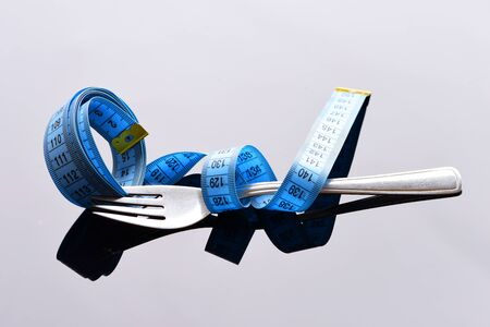 Fork belted with blue measuring tape isolated on light grey background with reflection. Symbol of food limitations and diet