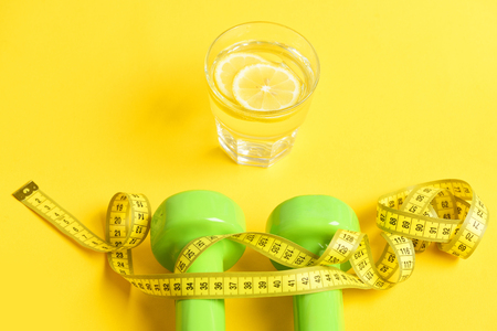 dumbbells twined by measuring tape with freshly squeezed glass of citrus on yellow background