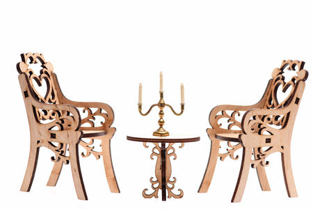 candelabrum with candle on table and decorative wooden chairs have heart on back isolated on white background, side view