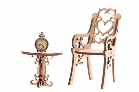 Antique concept. Alarm clock in golden color on decorative wooden table with chair have heart on back isolated on white background Stock Photo