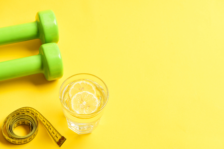 diet concept with dumbbells, measuring tape and lemon water on yellow background. Top view, copy space