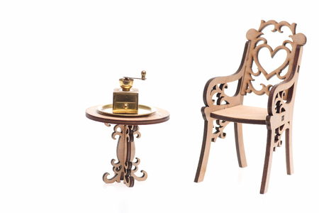 Coffee Grinder, antique vintage golden ware on tray on decorative wooden table with engraved chair isolated on white background
