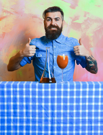 Bearded man, long beard. Brutal caucasian tattooed smiling hipster with moustache in denim shirt with tropical alcohol fresh cocktail and flask on blue checkered plaid on colorful texture background