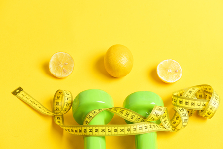 dumbbells twined by measuring tape with lemon and citrus slices on yellow background Stock Photo