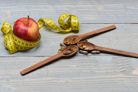 Concept of healthy nutrition, dietary supplement and diet alternatives. Red juicy apple wrapped with measuring tape next to wooden spoons with pills on vintage wooden background