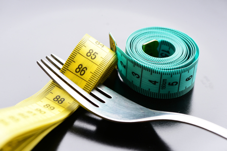 Roll of green measuring tape next to metal fork, which has folded yellow measuring tape between its tines on light grey background, close up