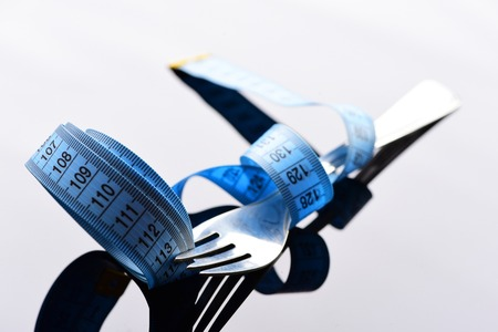 Fork and measuring tape around it and between its tines on light background with reflection. Symbol of weight management