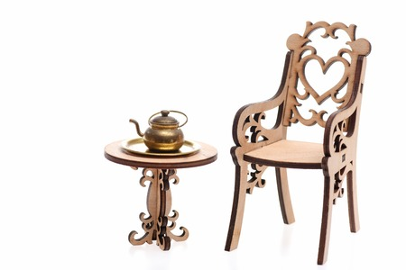 Antique teapot on decorative wooden table with engraved chair isolated on white background