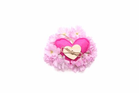 Handmade pink cloth heart decorated with wooden button and twine placed in wreath of light pink sakura flowers isolated on white background, top view and copy space Stock Photo