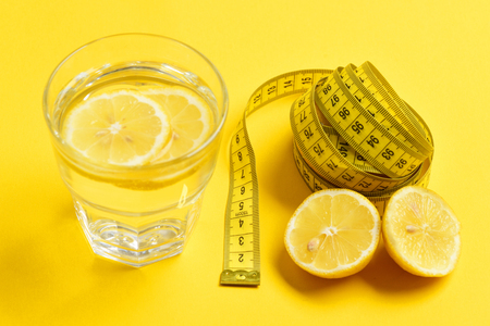 Measuring tape, lemon with freshly squeezed glass of citrus on yellow background. Nutrition and diet concept