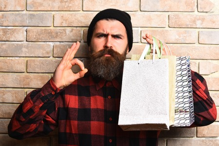 money packs: Bearded man, long beard. Brutal caucasian serious hipster with moustache holding shopping packages in red black checkered shirt on beige brick wall studio background