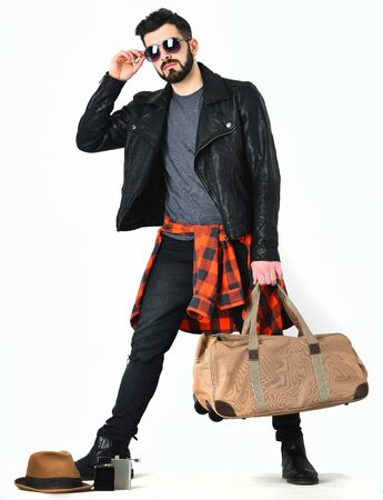 Bearded man, short beard. Caucasian serious hipster with moustache holding stylish bag, wearing black leather jacket, checkered red shirt and ripped jeans isolated on white background Stock Photo