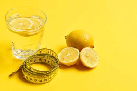 measuring cup: centimeter, lemon with freshly squeezed glass of citrus on yellow background. Nutrition and diet concept Stock Photo