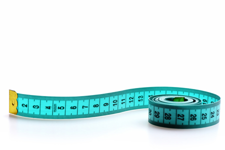 Roll of greenish blue flexible ruler with metal golden ends and black numbers isolated on white background with copy space