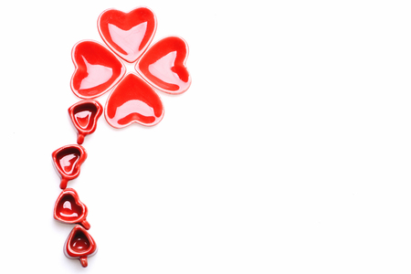heart shaped: Heart plates shamrock. Red heart shaped saucers and red cups making clover shape isolated on white background, top view and copy space. Valentines day luck