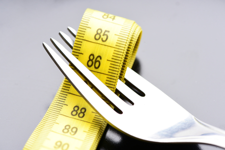 Fork holds folded yellow tape for measuring between its tines, isolated on light grey background, close up