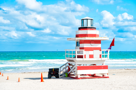 South Beach, Miami, Florida, lifeguard house in a colorful Art Deco red and whhite style on cloudy blue sky and Atlantic Ocean in background, world famous travel location