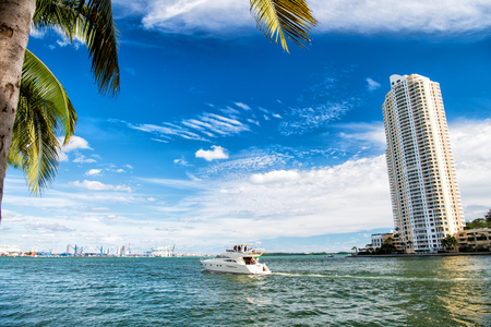 Downtown Miami along Biscayne Bay with condos and office buildings, yacht sailing in the bay at sunny day