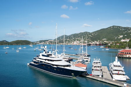 Saint Thomas, USA - January 13, 2016: beautiful black yacht, luxury modern motor vehicle enters blue sea port or harbor with sailboats, boats on sunny summer day on green mountain background