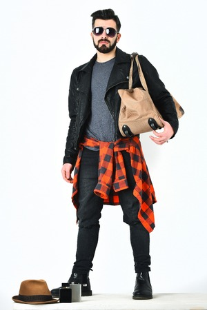 Bearded man, short beard. Caucasian hipster with moustache holding casual stylish bag wearing black leather jacket, checkered red shirt and ripped jeans isolated on white background