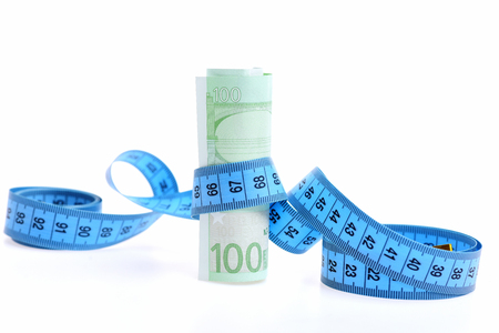 roll of euro money with measuring tape isolated on white background