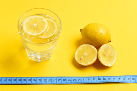 tape-measure, lemon with freshly squeezed glass of citrus on yellow background. Nutrition and diet concept