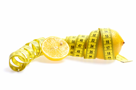 Fruit and diet concept. Tape-measure twined around lemon isolated on white background, copy space Stock Photo