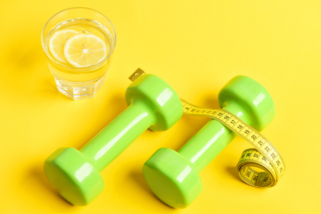 remedy for weight concept. freshly squeezed glass of citrus with dumbbells twined by measuring tape on yellow background
