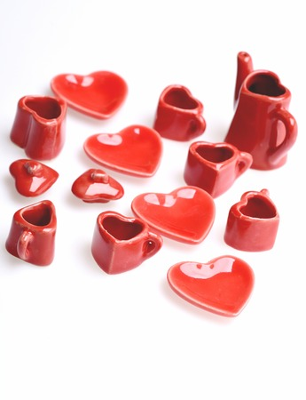 Plates in shape of heart and other tiny dishes in red colour made of clay isolated on white background, close up and selective focus. Valentines day story